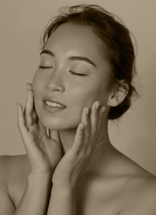 A woman with clean and fresh skin, touching her face and smiling